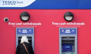 A customer uses an RBS branded automated teller machine (ATM), at a Tesco Bank cash point