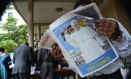 A man reads a newspaper bearing an image of Pope Francis in Nairobi