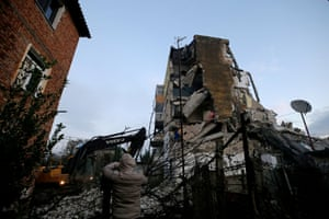 Man taking a picture of a collapsed building