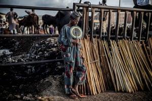 A Hausa-Fulani man selling herdsmen's sticks waits for customers at Kara cattle market in Lagos