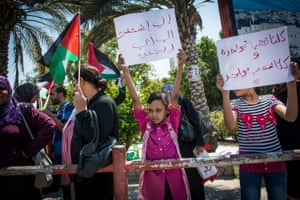 A young girl hold up a sign saying 'I really miss my dad. Bring him back home' at weekly protest for women against the partition of Gaza and the West Bank