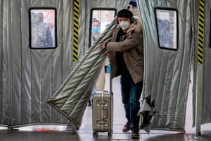 A passenger wearing a protective mask enters Beijing West railway station on 24 January 2020.