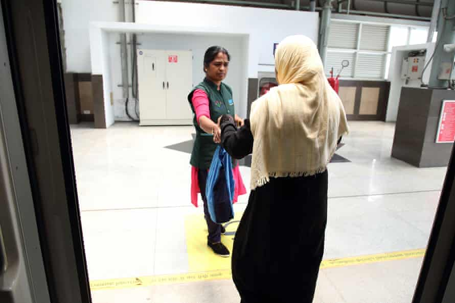 A Kudumbhashree member hands a Koshi Metro worker her lunch