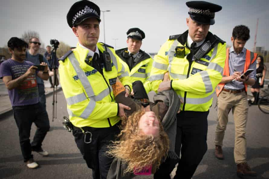 Police officers carry away an Extinction Rebellion protester on Waterloo Bridge in London in April 2019