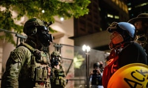 A federal agent faces off with a protester outside Portland's downtown courthouse.
