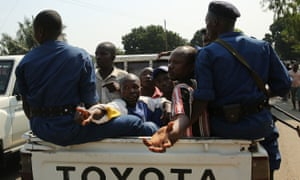Police guard men after they were rounded up by supporters of President Pierre Nkurunziza and accused of being opposition party members, in Rumonge, Burundi