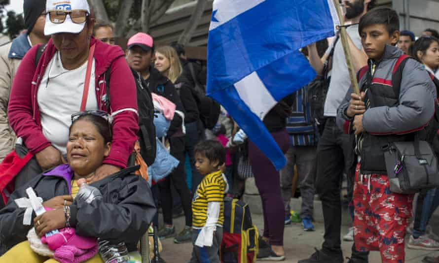 Members of a caravan of Central Americans wait at Tijuana on the Mexico-US border. The boy at right is holding a Honduran flag.