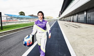 Jamie Chadwick in her racing gear and holding her helmet, walking on the track at Silverstone.
