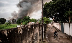 A man rides his bike as smoke rises from a fire at the independent national electoral commission's (CENI) warehouse in Kinshasa.