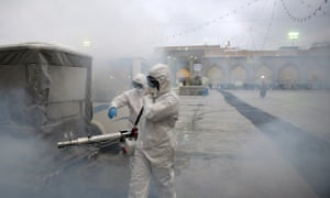 Members of a medical team spray disinfectant at Imam Reza's shrine in Mashhad, Iran