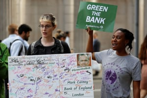 An anvironmental and banking system protestor holds a petition card which was signed at Glastonbury festival before being handed in as they demonstrate outside the Bank of England demanding that the bank rule out investment in high-carbon sectors in London.