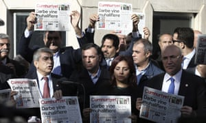 Journalists and politicians hold copies of the opposition Cumhuriyet newspaper in Istanbul.
