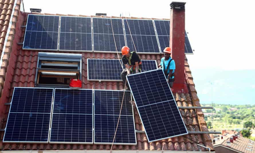 Workers install solar panels on the roof of a home in Colmenar Viejo, Spain.