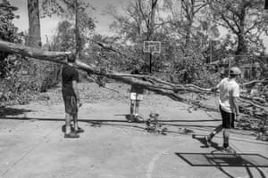 Kids remove storm debris from a park basketball court in Newhall, Iowa.