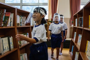 Children wear face shields to the library in Kinugawa elementary school in Nikko, Japan