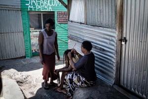Women braid each others hair in an alleyway