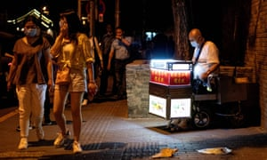 A street vendor selling sweets waits for customers along a street in Beijing on 11 June