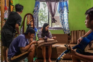 Donna's children spending time together in their home in Tublay, Philippines. Two of them are looking at their phones