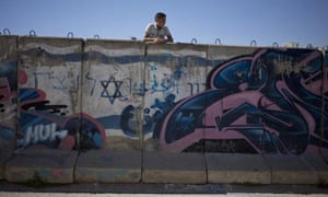 A Palestinian boy looks behind a wall separating the Jewish and Palestinian parts of Hebron in the West Bank. Barack Obama said a lack of progress in peace efforts made a continued US veto at the UN on resolutions condemning Israel more 'difficult'.