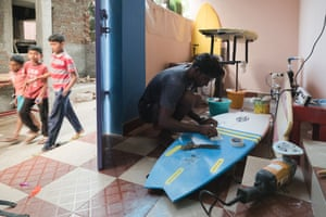 Raghul Panneerselvam making surfboards. As well as being a talented surfer, Raghul Panneerselvam also makes surfboards, and uses his family's porch as a repair shop.