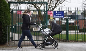 A woman pushes a pram past Mossley C of E primary in Congleton, England.