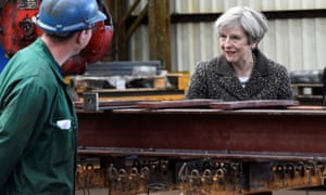 Theresa May talking to a worker as she visits a steel works in Newport, Wales, today.