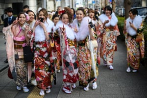 Women wearing kimonos gesture at the camera.