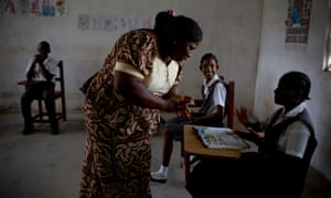 Geraldine (Pinky) Jones signs to a pupil at the Oscar Romero school in Tubmanburg.