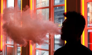 A patron exhales vapor from an e-cigarette at a store in New York.