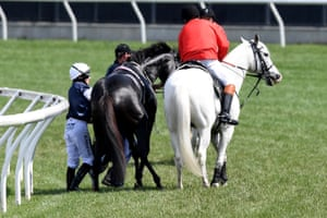 Jockey Aiden O'Brien on The CliffsofMoher is assisted by a race steward after the horse was injured during race 7.