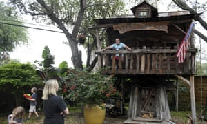 Dr. Jason Barnes, top right, sits in his kids' treehouse while his family plays in their backyard Saturday, 18 April 2020, in Corpus Christi, Texas.