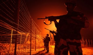 Indian soldiers guard a border fence at an outpost along the line of control in Suchit-Garh
