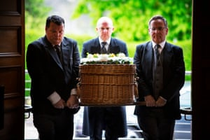 Greeted by a lone piper, Eddie's wicker coffin arrives at the crematorium