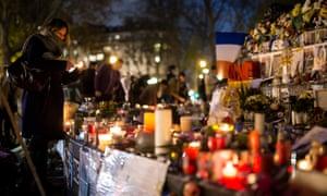 A woman lights a candle for the victims of the terrorist attacks at Place de la République, Paris.