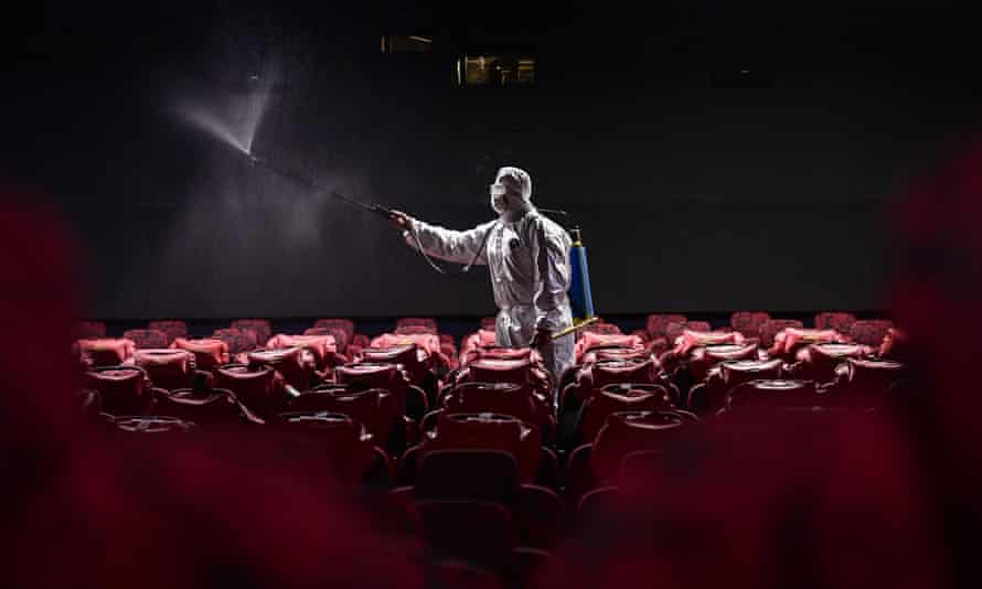 A staff member sprays disinfectant at a Shenyang cinema on 25 March.