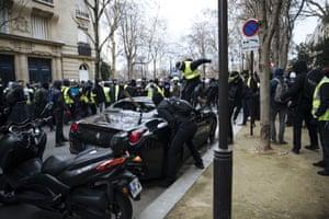 Paris, France: Gilets jaunes protesters attack a luxury car
