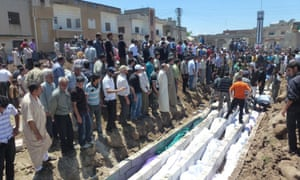 People in Syria watching the mass burial of victims of the Houla massacre in 2012