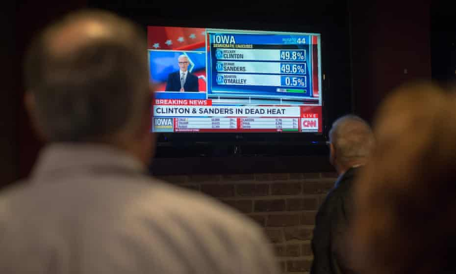 People look on as a television broadcast declares Senator Bernie Sanders and Hillary Clinton in a dead heat