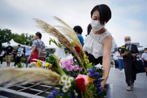 A woman offers a flower before praying for the victims