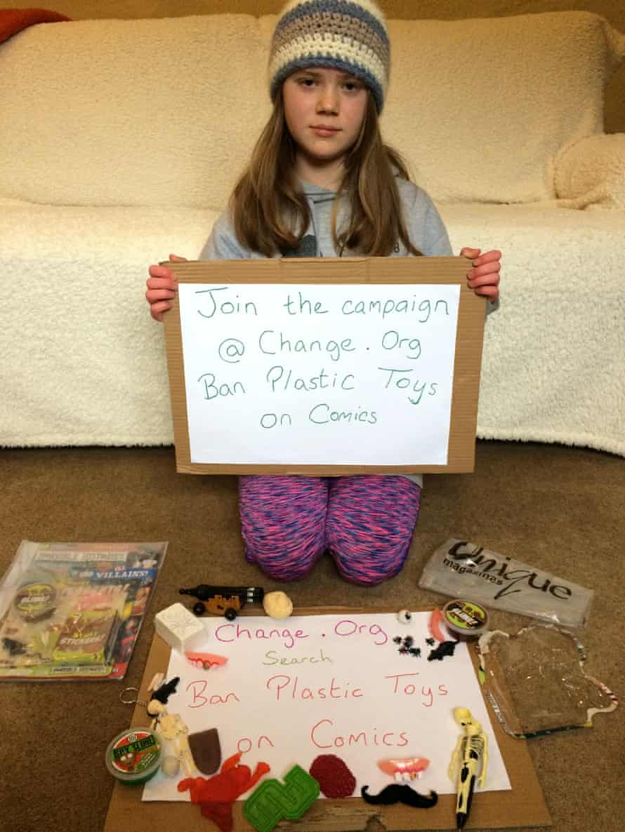 Skye Neville holds a placard reading: 'Join the campaign @ change.org Ban Plastic Toys on Comics'
