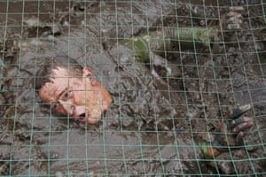 A participant crawls through the mud during the Race of Heroes event in Novosibirsk, Russia