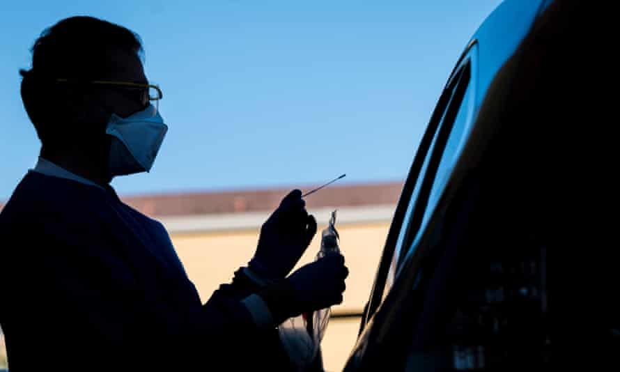 A medical worker administers a swab test at a Covid-19 drive-thru testing site in San Pablo, California.