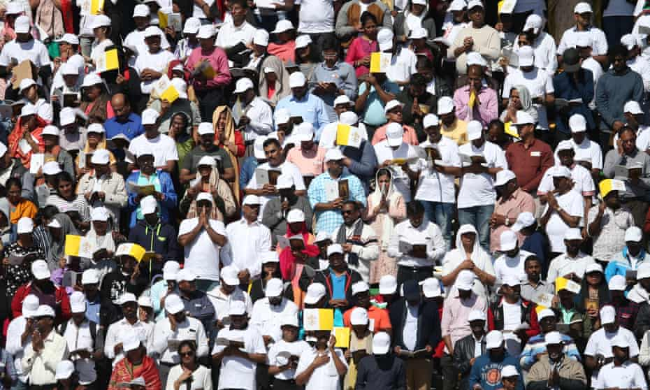 People watch Pope Francis deliver mass during his three-day visit to the UAE