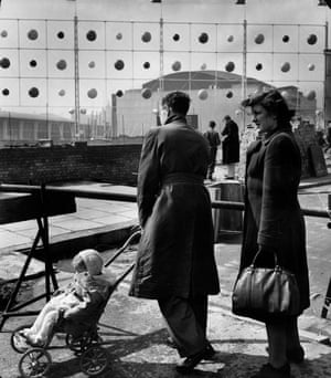 A family walks outside the festival site. The Royal Festival Hall can be seen behind Ed Mills' Abacus screen. Architects designed screens to shield the site from the surrounding roads and Waterloo Station. (GNM Archive ref: JHB/1/3/43 box 3)