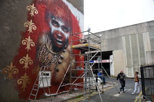 British street artist, Dale Grimshaw, (second right) creates an artwork.
