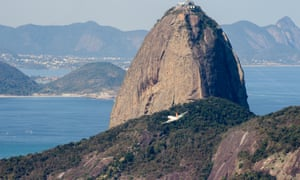 Visitors continue to arrive, flying past Sugar Loaf Mountain as seen from the Dona Marta viewpoint and favela Santa Marta