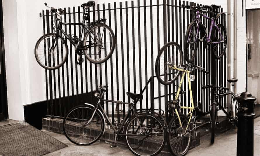 Bicycles chained to railings up in the air and off the ground in Soho in London