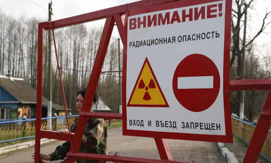 A Belarussian guard opens gate at a check-point in the exclusion zone around the Chernobyl nuclear reactor.