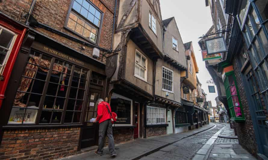 A postman delivers mail to shops in the Shambles in York