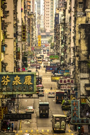I grabbed this image while walking across a covered bridge in Hong Kong. Using a zoom lens has pulled the foreground closer, making what is a very long street seem shorter, focusing on all the signs and clothes hanging from the buildings.